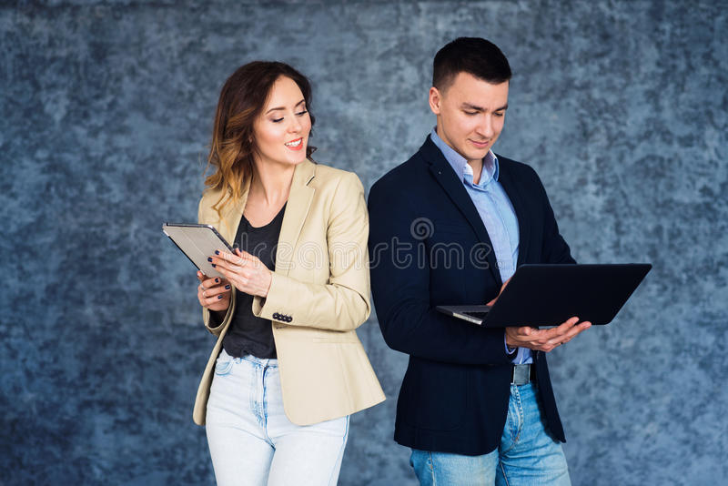 Business people woman and man standing opposite gray wall and holding tablet and laptop. Business partners communicating at meeting stock image