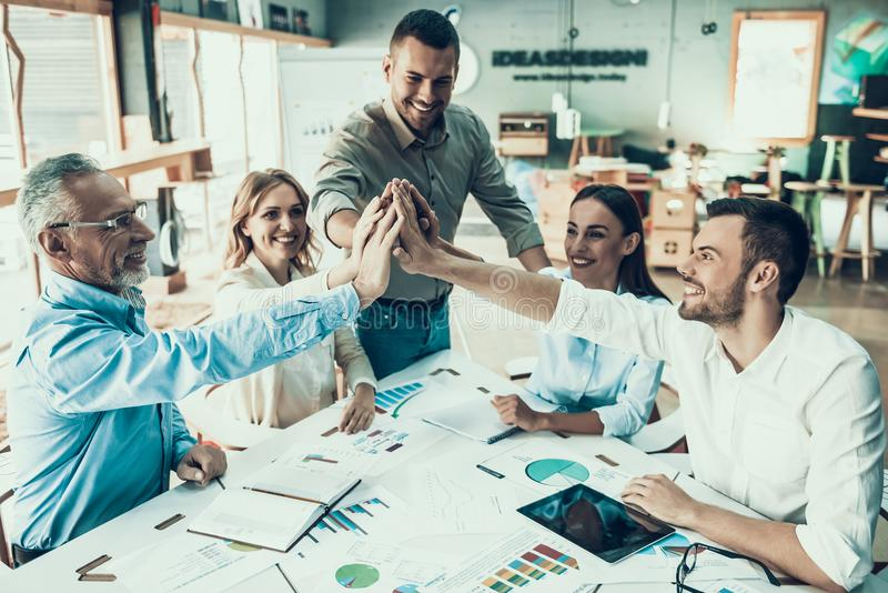 Business People at Work in Office Teamwork Concept. Group of Colleagues Sitting at Desk and Celebrating and Cheering each other for Work done. Comunication stock image