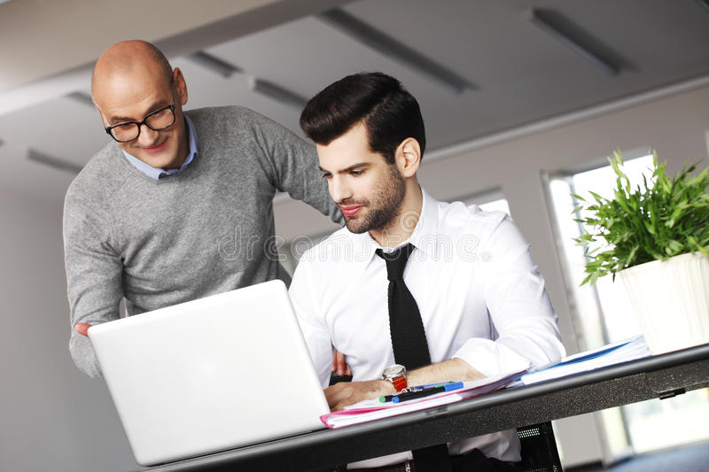 Business people at work. Portrait of young businessman sitting in front of laptop and consulting with financial manager. Teamwork at office stock images