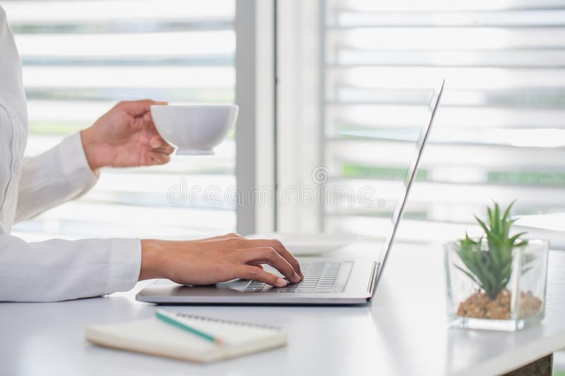 Business people work Put your hand on the laptop keyboard.The other hand is holding a coffee cup. The concept of online networking royalty free stock image