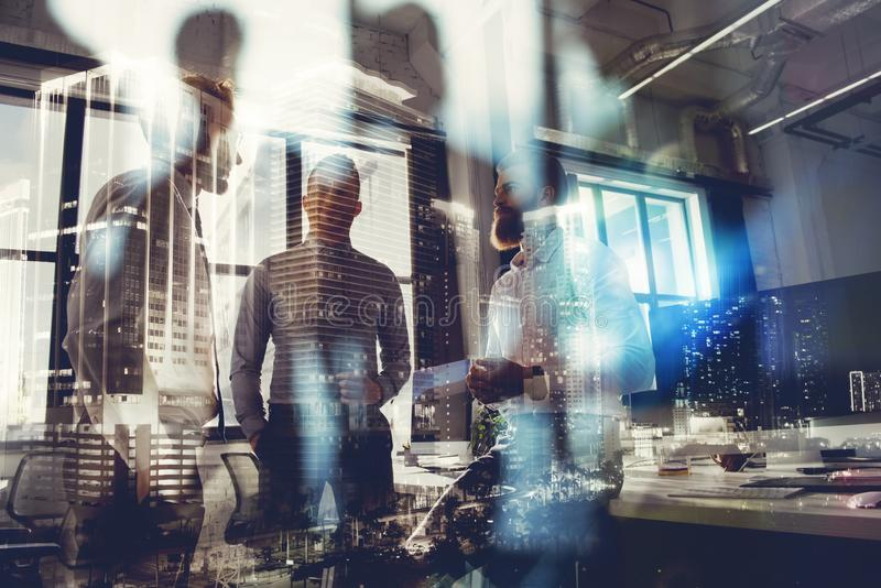 Business people work together in office. Concept of teamwork and partnership. double exposure with modern city and light royalty free stock image