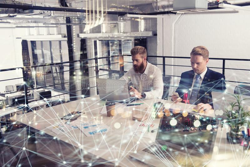 Business people that work together in office at the night with network effects. Concept of teamwork and partnership stock image
