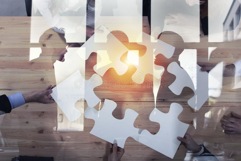 Business people work together to build a puzzle. Concept of teamwork, partnership, integration and startup. double. Business people work together in office to stock image