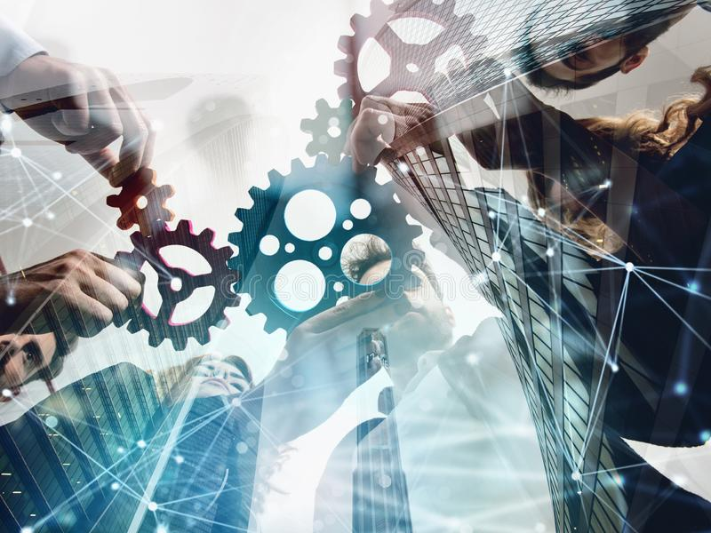 Business team connect pieces of gears. Teamwork, partnership and integration concept. double exposure with network stock illustration