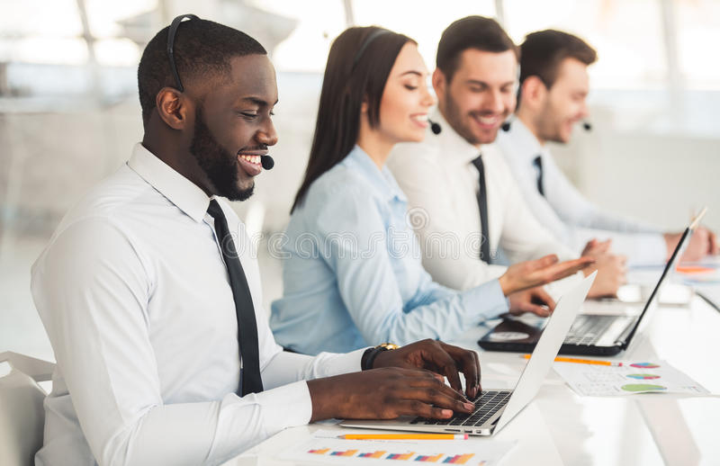 Business people working. Attractive business people in suits and headsets are smiling while working with laptops in office stock photography