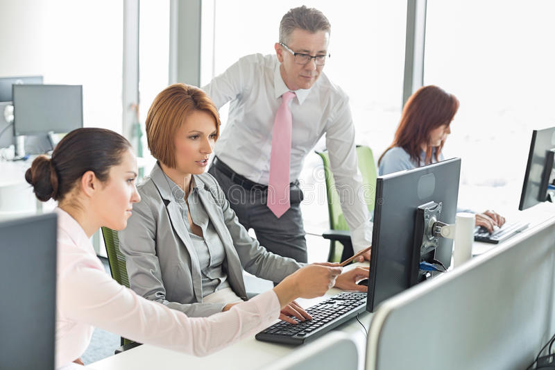 Business people working on computer in office stock photography