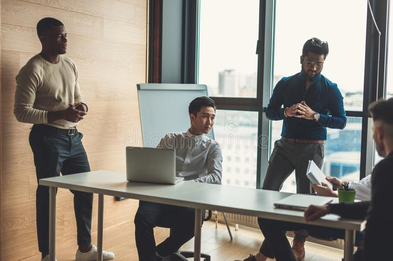 Business people working in conference room in modern loft office. Multiethniorporate business team reporting the Head of department about the results of done stock images