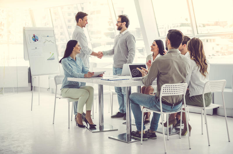 Business people working. Business people at the conference. Two men are shaking hands while others are applauding royalty free stock image