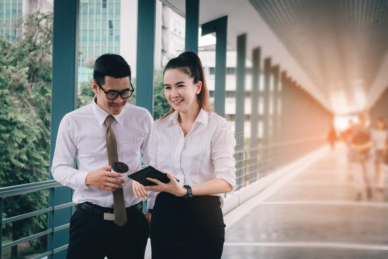 Business people working on digital tablet and analysis chart report together at walkway in company building.  royalty free stock image
