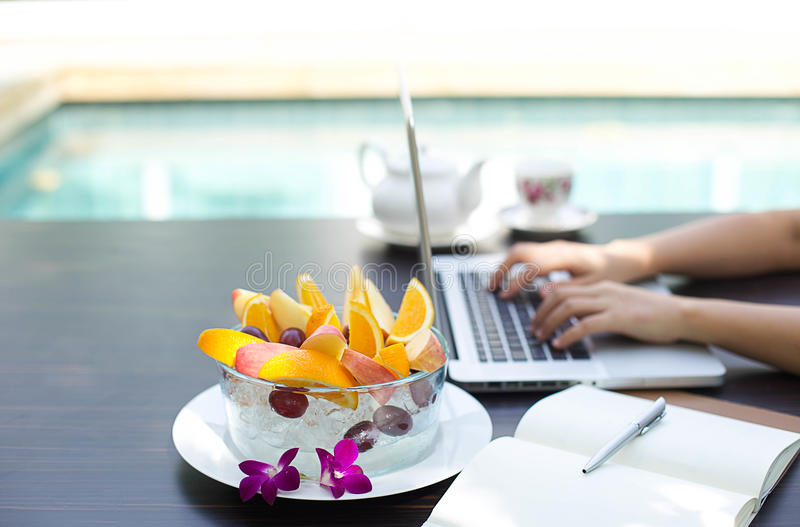 Business people working at home. On laptop computer with blows of fresh fruit by swimming pool royalty free stock image