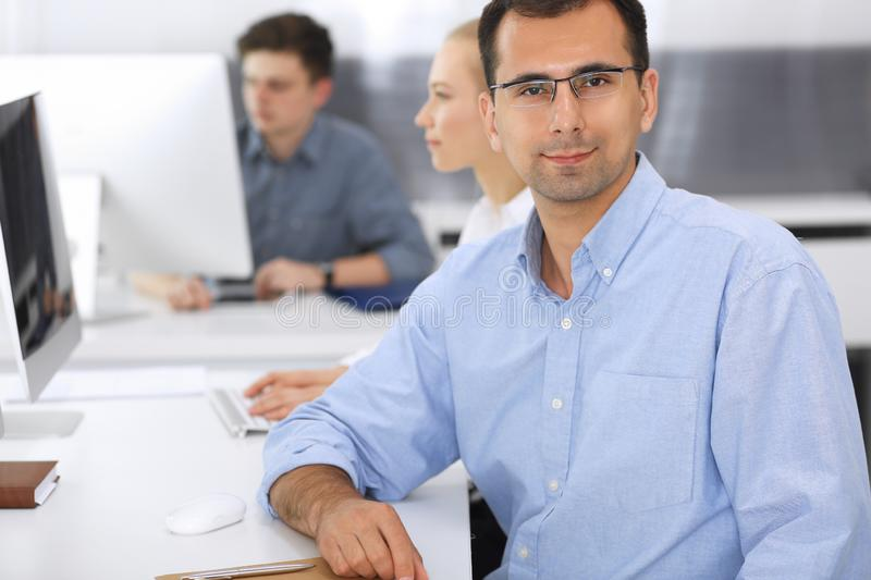 Business people working together in modern office. Focus at happy smiling adult businessman or entrepreneur using pc royalty free stock photos