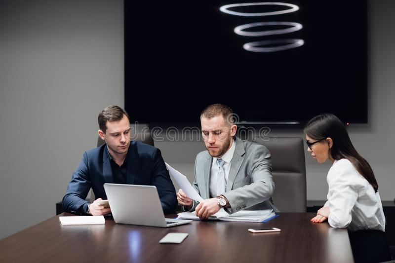 Business people working together on their laptop in a meeting room stock image