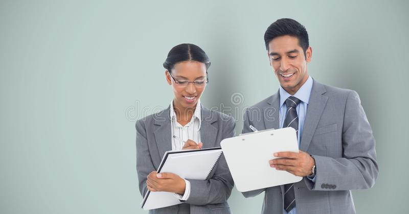 Business people writing against gray background royalty free stock photos