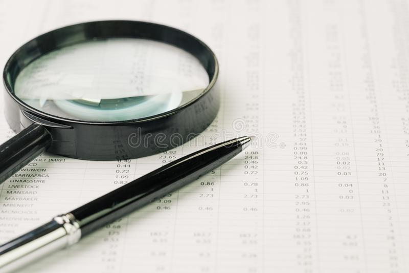 Business perfomance review, searching or chasing for investment. Return concept, magnifying glass and pen on performance, price numbers report print paper on stock images