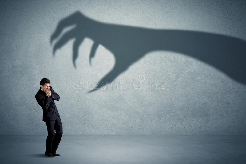 Business person afraid of a big monster claw shadow concept. On background royalty free stock photography