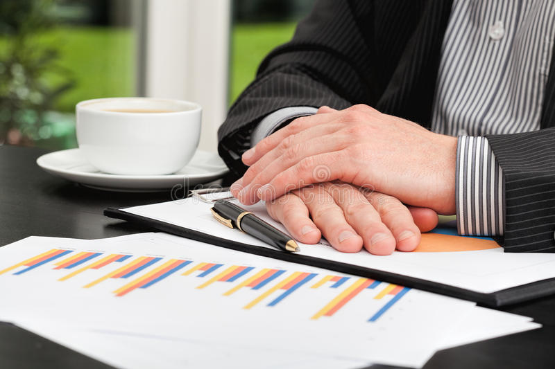 Business person analyzing a bar charts. Business person with hands crossed analyzing a bar charts stock images