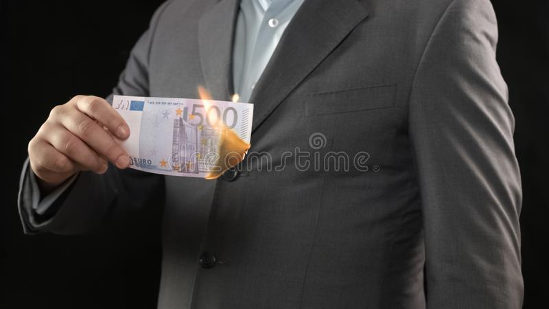 Business person burning five hundred euro bill, money wasting bankruptcy concept. Stock photo royalty free stock photos