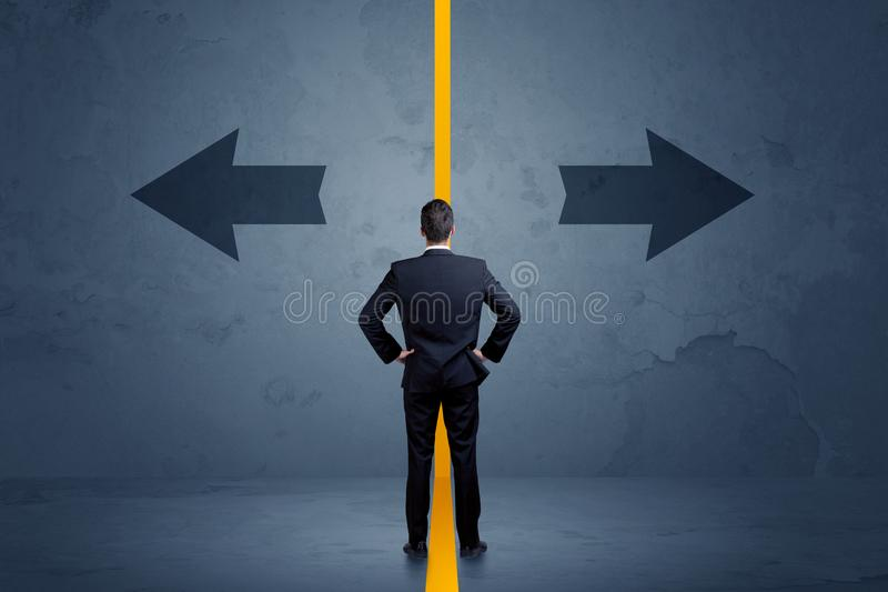 Business person choosing between two options separated by a yell. Ow border arrow concept royalty free stock photo