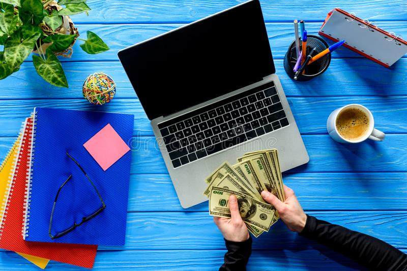 Business person counting dollars by laptop on blue wooden table royalty free stock photography
