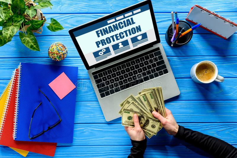 Business person counting dollars by laptop on blue wooden table with stationery, Financial stock image