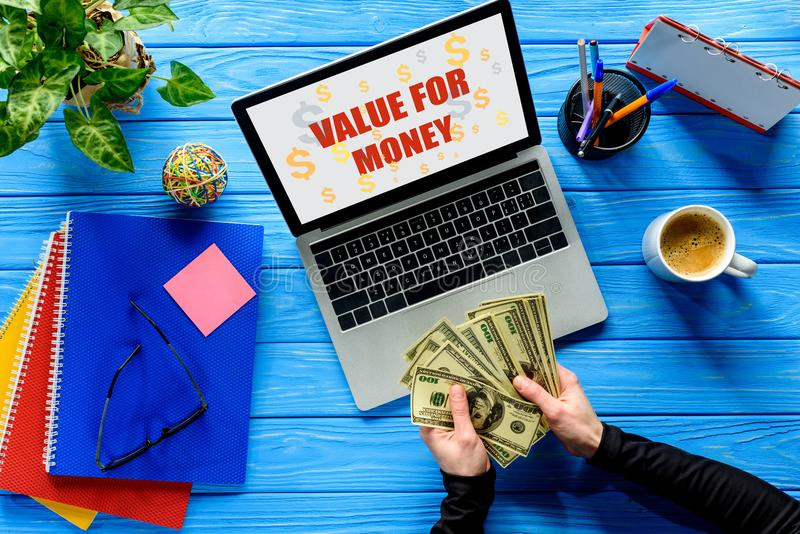 Business person counting dollars by laptop on blue wooden table with stationery, Value stock photography