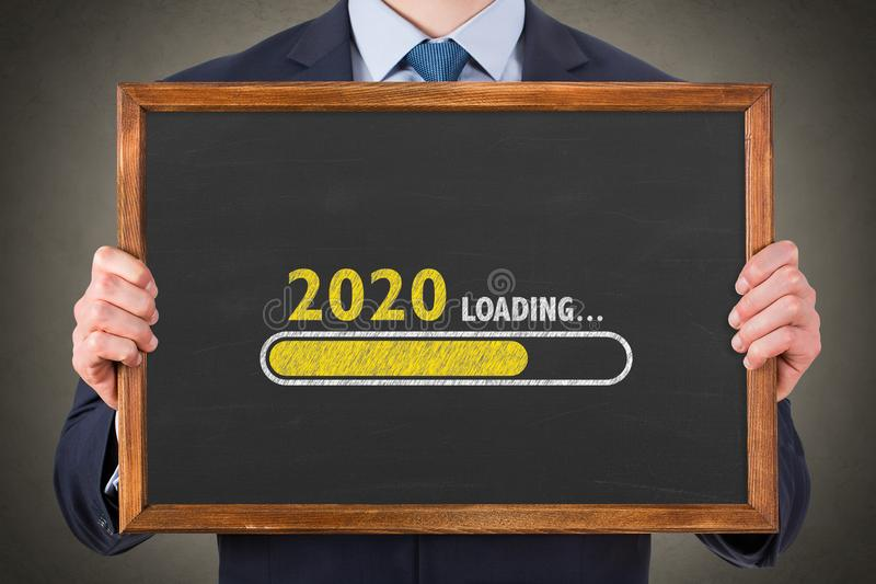 Business Person Drawing Loading New Year 2020 on Chalkboard Background stock photos