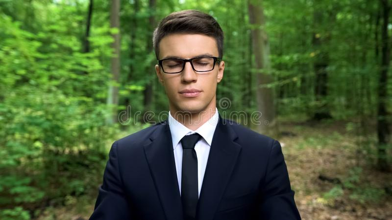 Business person feeling inner harmony in forest, finding body and mind balance stock images