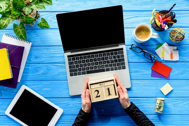 Business person holding calendar by laptop on blue wooden table stock photography
