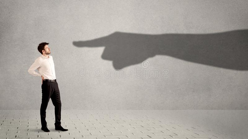 Business person looking at huge shadow hand pointing at him concept. On background stock photos
