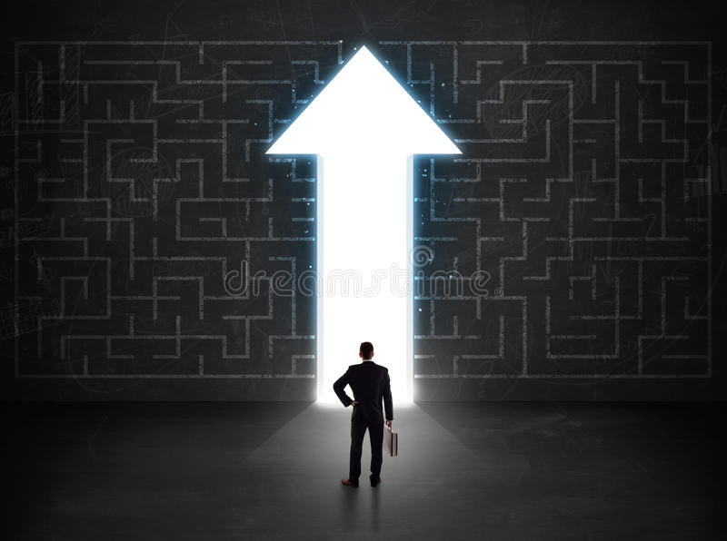 Business person looking at maze with solution arrow on the wall stock photos