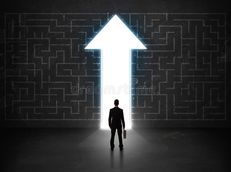 Business person looking at maze with solution arrow on the wall royalty free stock photography