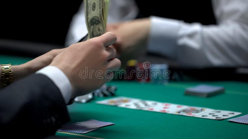 Business person pulling money out of wallet, risky poker game, bluff gambling. Stock photo stock photo