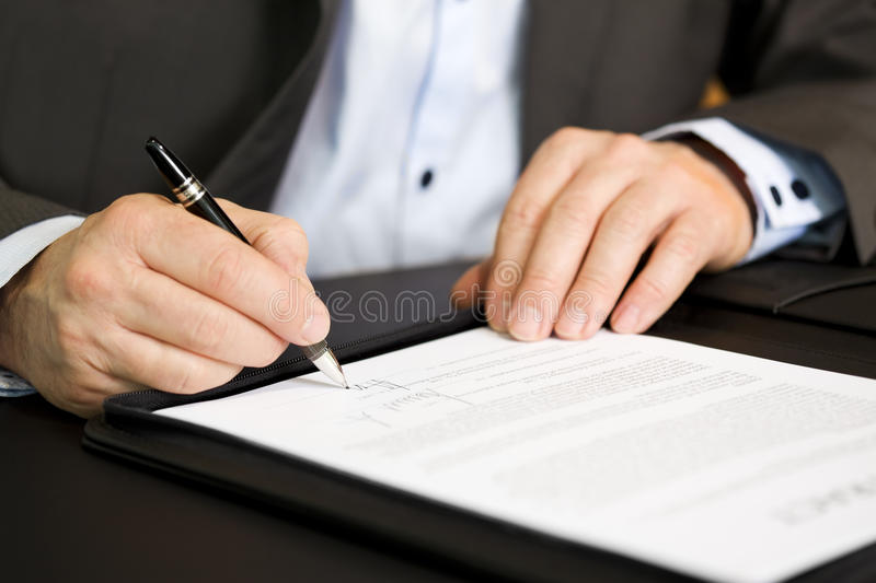 Business person signing a contract. Businessman in dark suit and blue shirt sitting at office desk signing a contract with shallow focus on signature royalty free stock photos