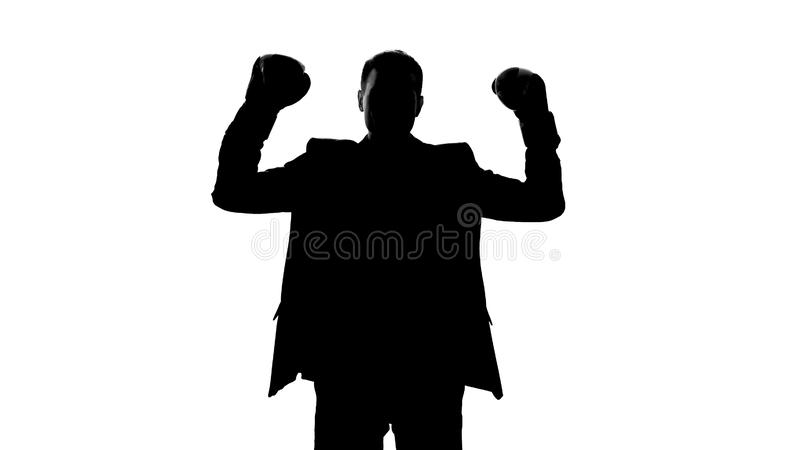 Business person silhouette in boxing gloves celebrating successful deal, emotion. Stock photo royalty free stock image