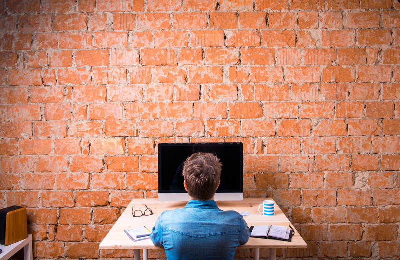 Business person sitting at office desk working, rear view. Business person sitting at office desk, working, against brick wall. Computer on the table. Coffee cup royalty free stock photo