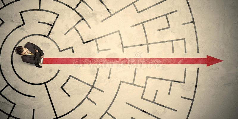 Business person standing in the middle of a circular maze. With red arrow stock photo