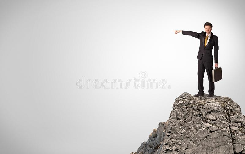 Business person on the top of the rock with copy space royalty free stock photos