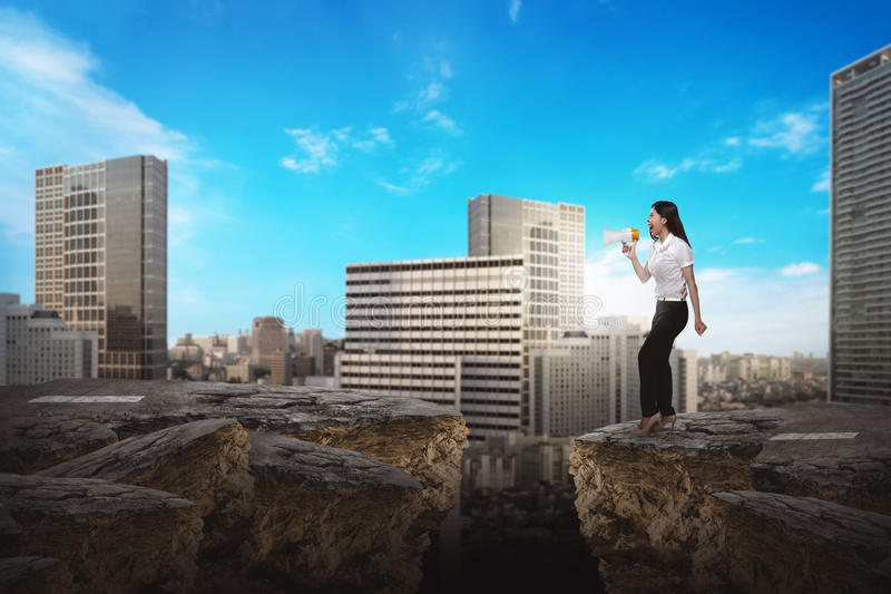 Business person using bullhorn. Asian business person talking with bullhorn on the broken road royalty free stock image