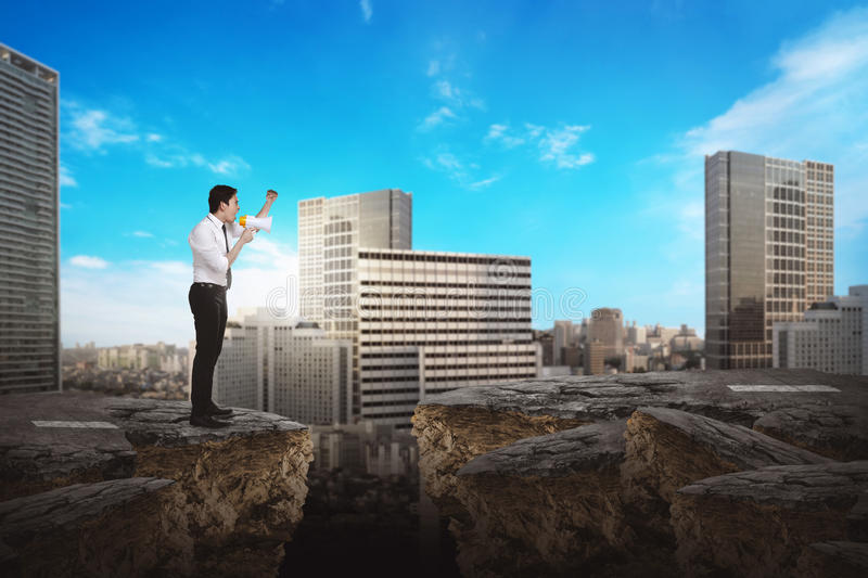 Business person using bullhorn. Asian business person talking with bullhorn on the broken road stock photography