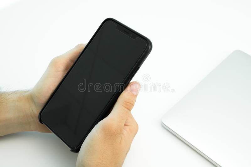 Business person using his smartphone on a white table. Modern workplace. Laptop stock image