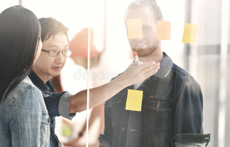 Business persons discussing work on a glass board royalty free stock photo