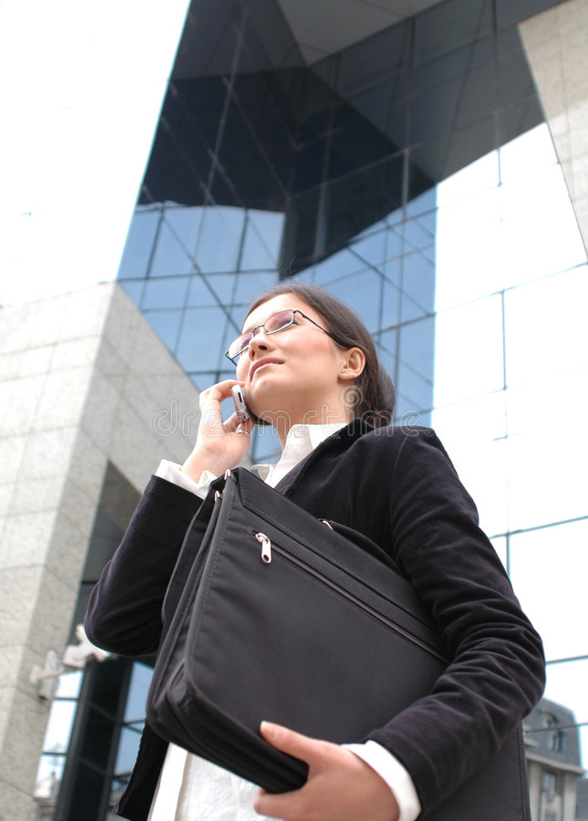 Business phone talk. Business woman on the phone, carrying a briefcase with documents