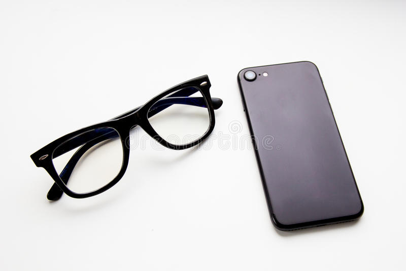 Business picture: smartphone and glasses. New generation black smartphone and glasses at white background royalty free stock image