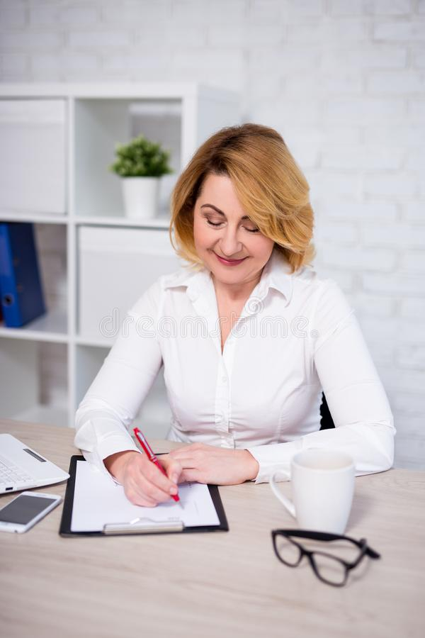 Business plan concept - cheerful mature business woman working in office royalty free stock images