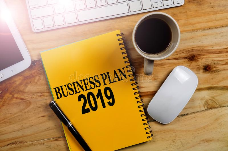 BUSINESS PLAN 2019 CONCEPT. Office desk table with laptop computer and coffee cup . Top view royalty free stock photo