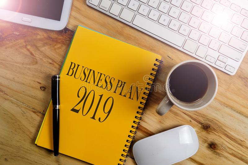 BUSINESS PLAN 2019 CONCEPT. Office desk table with laptop computer and coffee cup . Top view royalty free stock photography