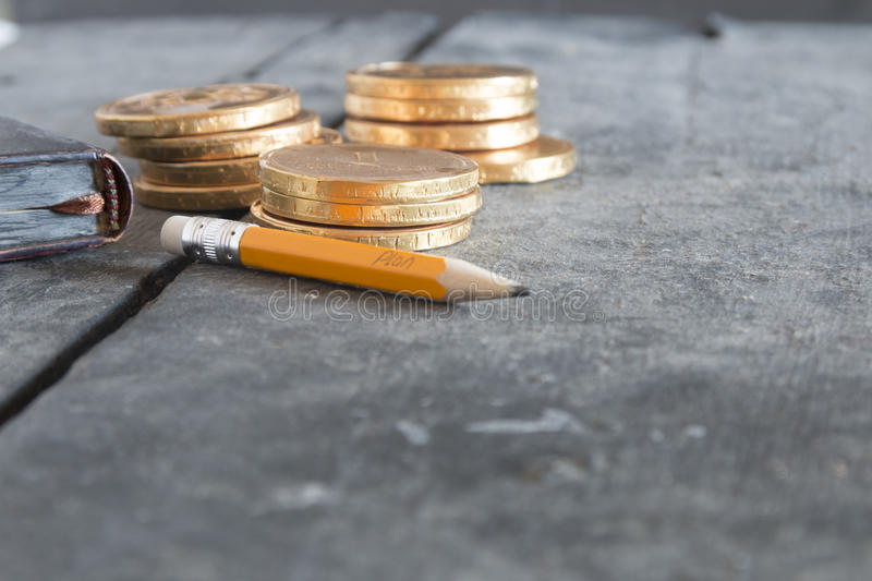 Business plan concept. Pencil with text and coins. royalty free stock photos