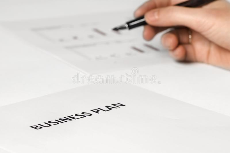 Business plan with hand + pen stock photography