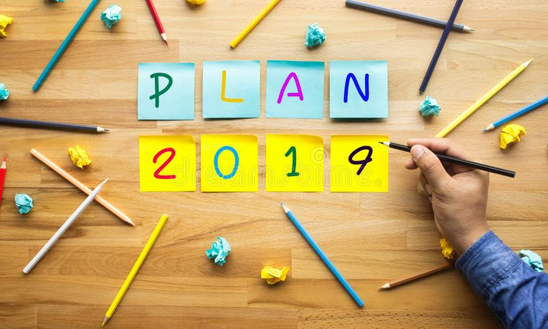 Business plan 2019 with male hand Writing pencil on notepaper royalty free stock images