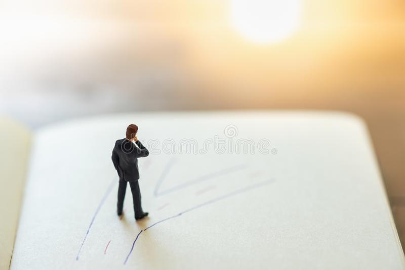Business planning and decision concept. Close up of businessman miniature figure standing on notebook with hand writing drawing stock photo